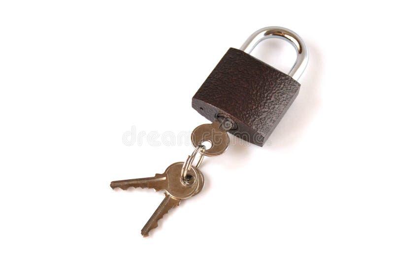 Candado marrón de textura bloqueado aislado con un manojo de tres llaves en un fondo blanco imágenes de archivo libres de regalías