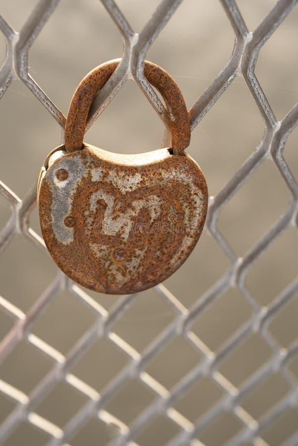 Candado oxidado en forma de corazón viejo en la cerca del metal foto de archivo