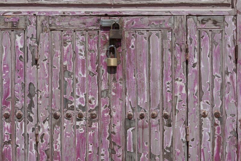 Candado oxidado que cierra una puerta de madera imagenes de archivo