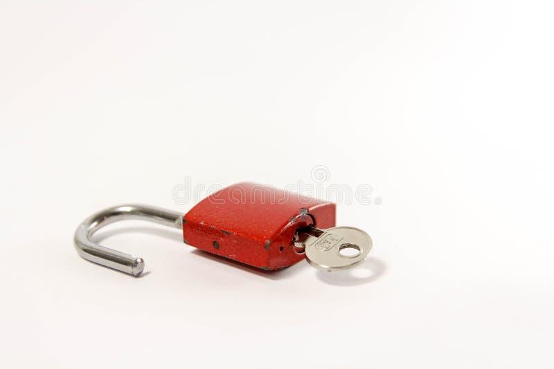 Candado rojo abierto y llave fotos de archivo