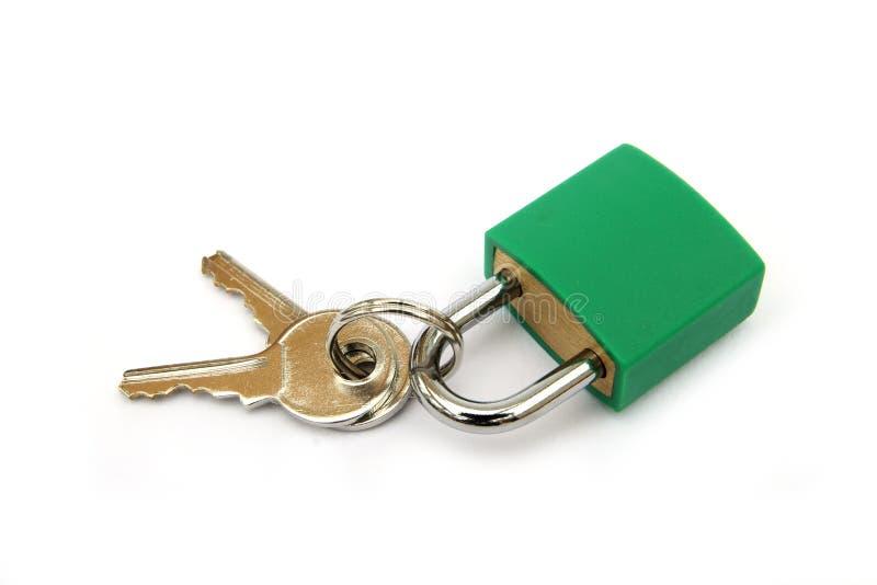 Candado verde, bloqueado, con dos llaves en el fondo blanco fotos de archivo libres de regalías