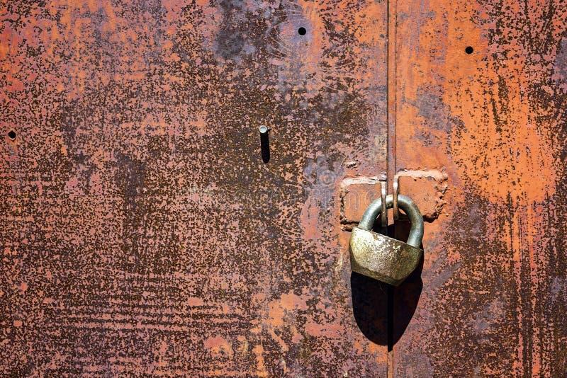 Candado viejo en una puerta oxidada del hierro imagen de archivo