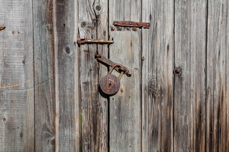Candado y cierre oxidados viejos en una puerta de madera fotos de archivo libres de regalías