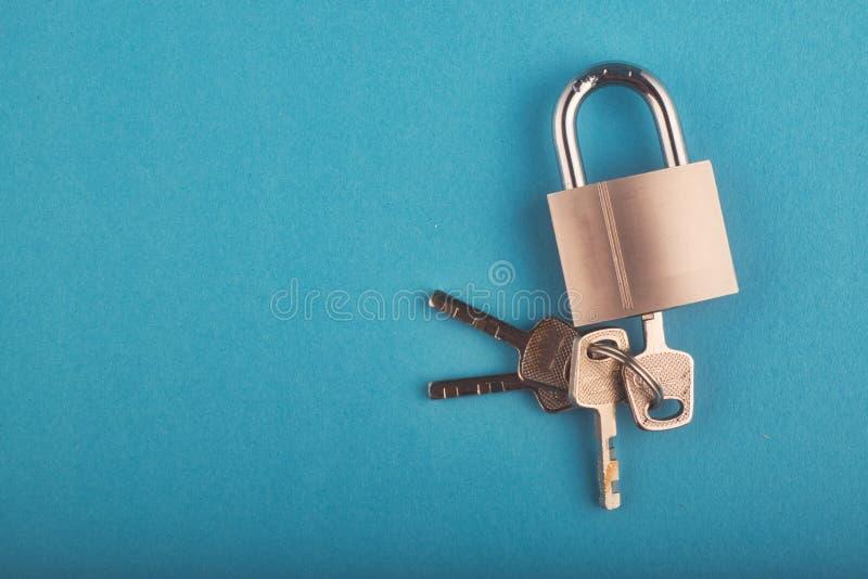 Candado y manojo de llave bloqueados en el fondo azul foto de archivo