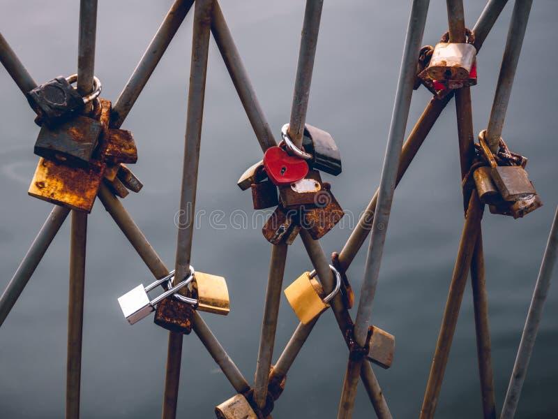Candados del amor encendido cerrados en las verjas en el puente imagen de archivo