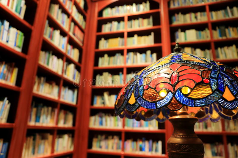 Candeeiro de mesa, livros e estante do vintage na biblioteca, conceito da sala de leitura velha da biblioteca imagem de stock royalty free