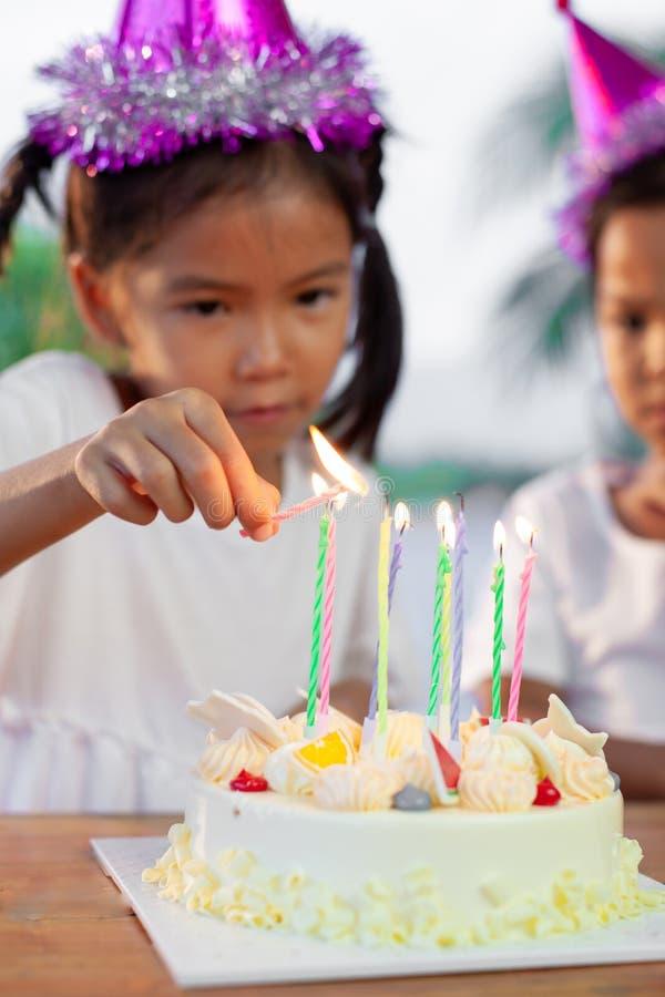 Candela asiatica di illuminazione della ragazza del bambino sulla torta di compleanno nella festa di compleanno immagini stock libere da diritti