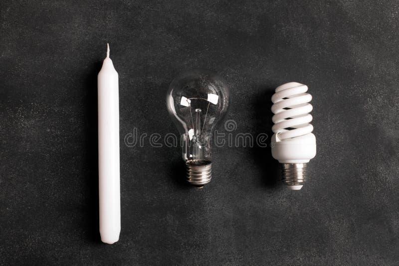 Candela bianca e lampadine elettriche sui precedenti neri immagine stock