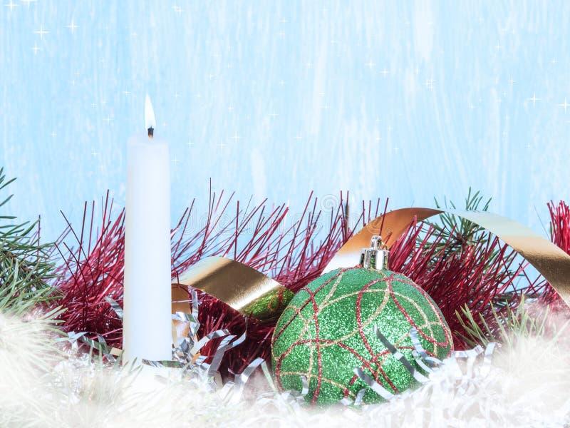 Candela bianca, una palla verde dell'albero di Natale, un lamé dell'albero di Natale Nuovo year& x27; fondo di s fotografia stock