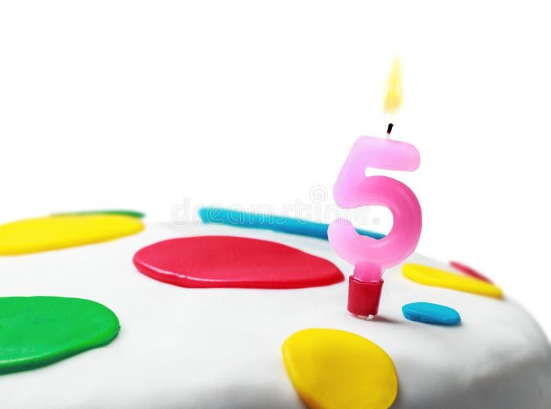 Candela bruciante con il numero cinque su una torta di compleanno fotografia stock libera da diritti