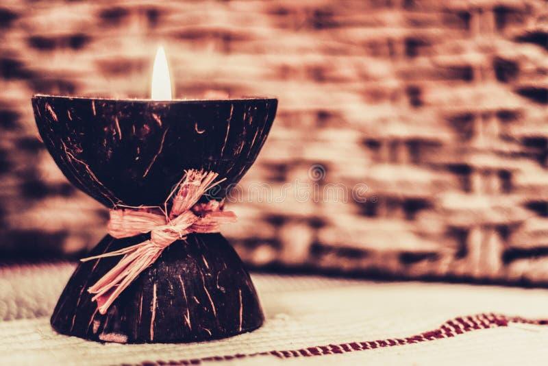 Candela bruciante dell'aroma della stazione termale nelle coperture della noce di cocco, interno domestico accogliente fotografia stock
