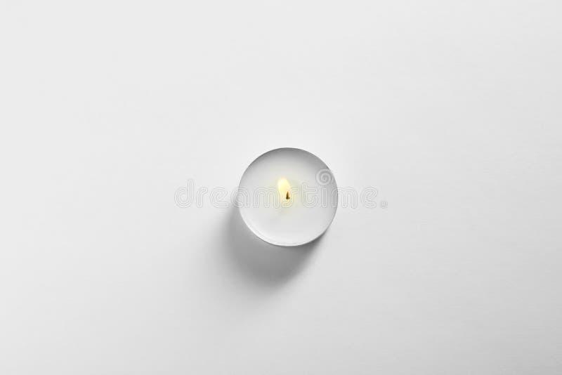Candela bruciante della cera sulla vista superiore del fondo bianco immagini stock