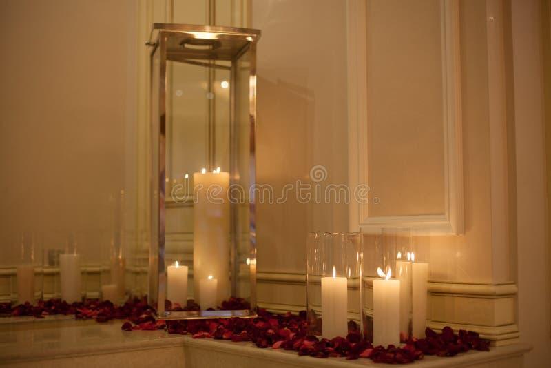 Candela circondata dai petali di rosa rossa con la riflessione vaga immagini stock libere da diritti
