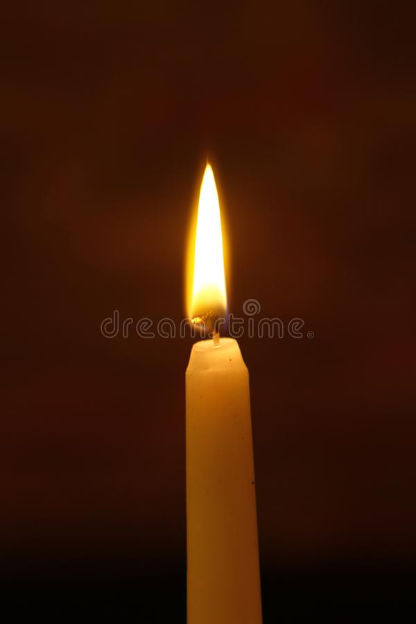 Candela d'ardore della grande cera con grande fuoco su fondo nero pesante fotografia stock libera da diritti