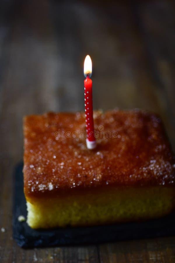 Candela di compleanno di Lit su un dolce immagine stock