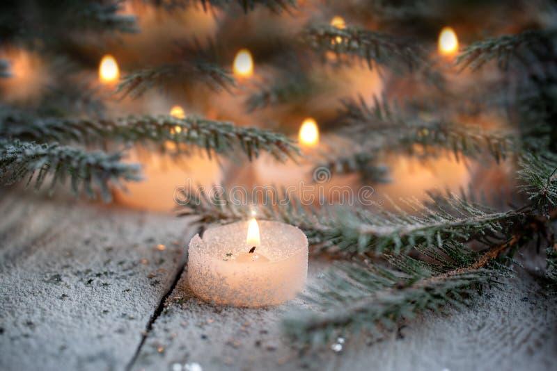 Candela e decorazione brucianti di Natale sopra neve con i rami del pino su fondo di legno bianco immagini stock