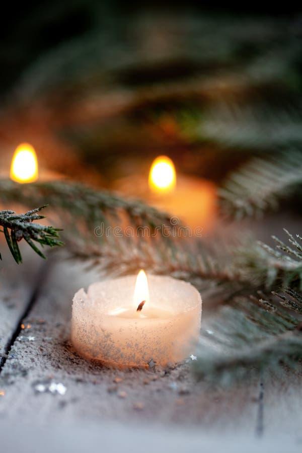 Candela e decorazione brucianti di Natale sopra neve con i rami del pino su fondo di legno bianco immagine stock libera da diritti