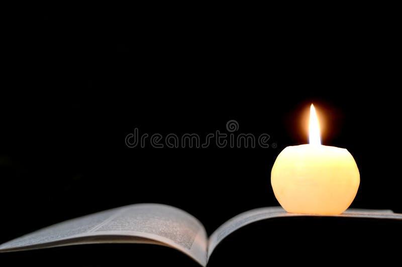 Candela e libro aperto isolati sul nero immagine stock libera da diritti