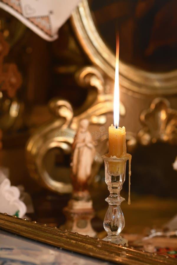 Candela fiammeggiare nella chiesa vicino alla figura della madre di Dio Cattolicesimo, il concetto di Cristianità fotografia stock libera da diritti