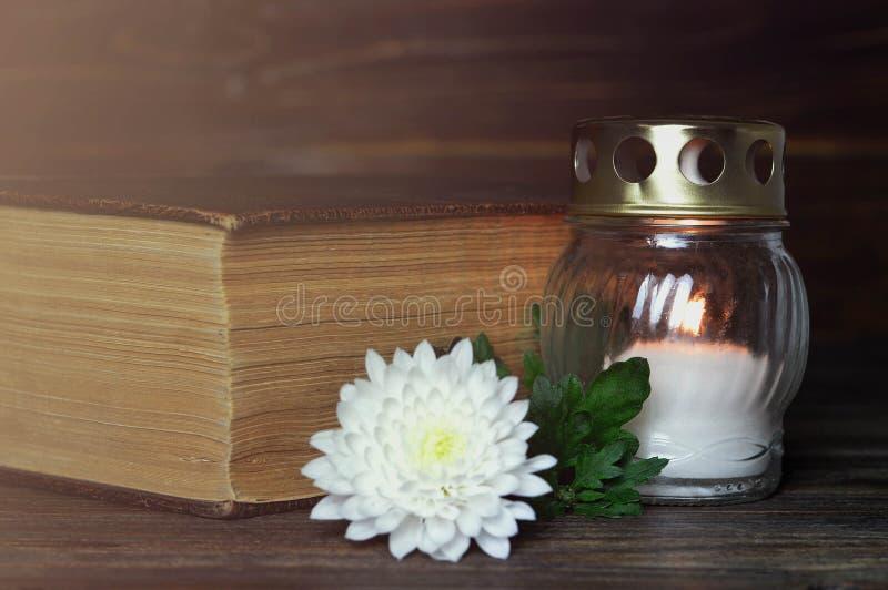 Candela, fiore del crisantemo e libro commemorativi bianchi fotografie stock