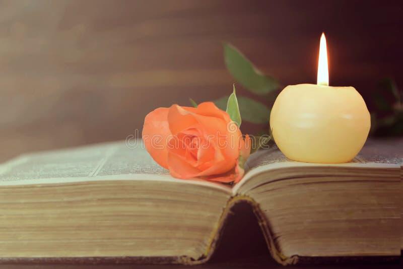 Candela, libro e fiore fotografie stock