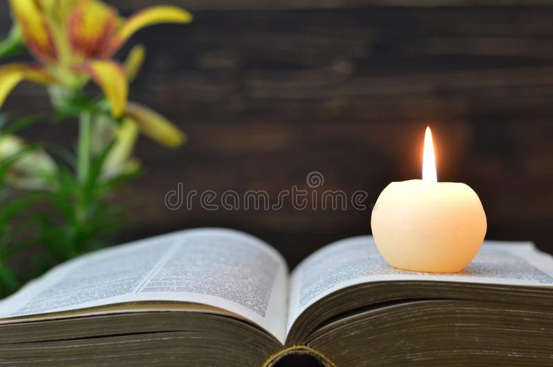 Candela, libro e fiori su fondo di legno fotografie stock