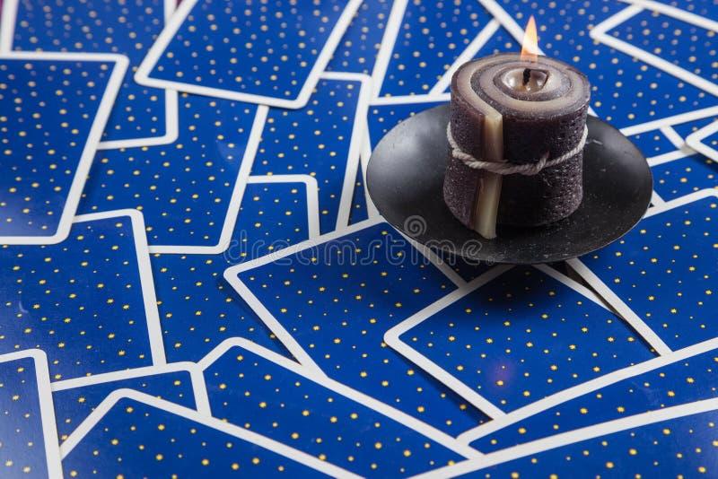 Candela nera disposta sulle schede di tarot dell'azzurro. fotografie stock