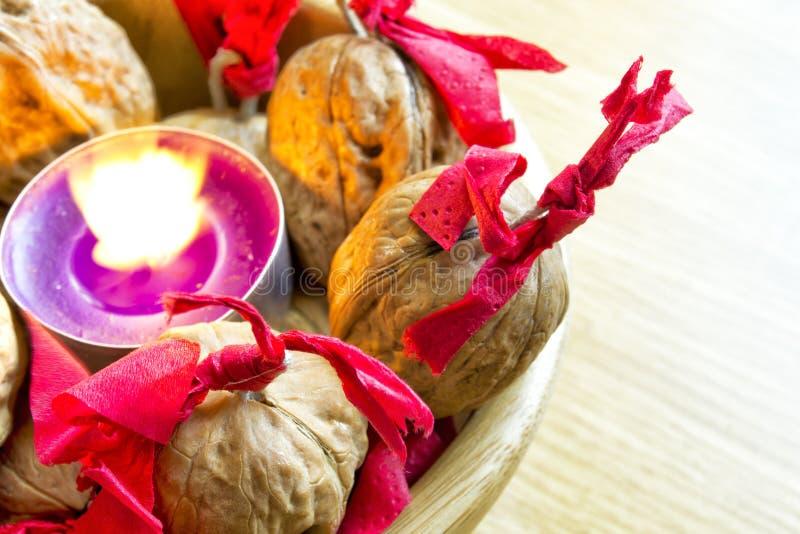 Candela porpora con i wallnuts decorati in una ciotola di legno immagine stock libera da diritti