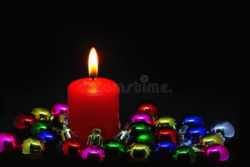Candela rossa con le piccole palle di Natale sul nero fotografia stock
