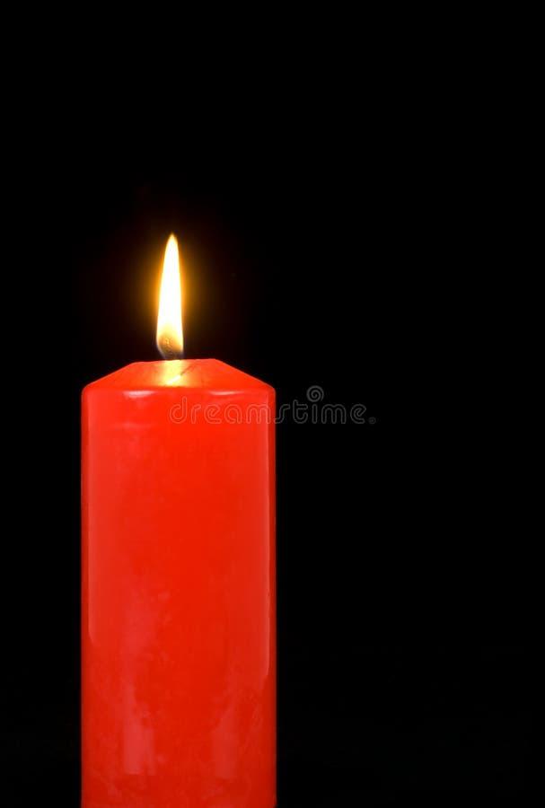Candela rossa illuminata sul nero immagini stock libere da diritti