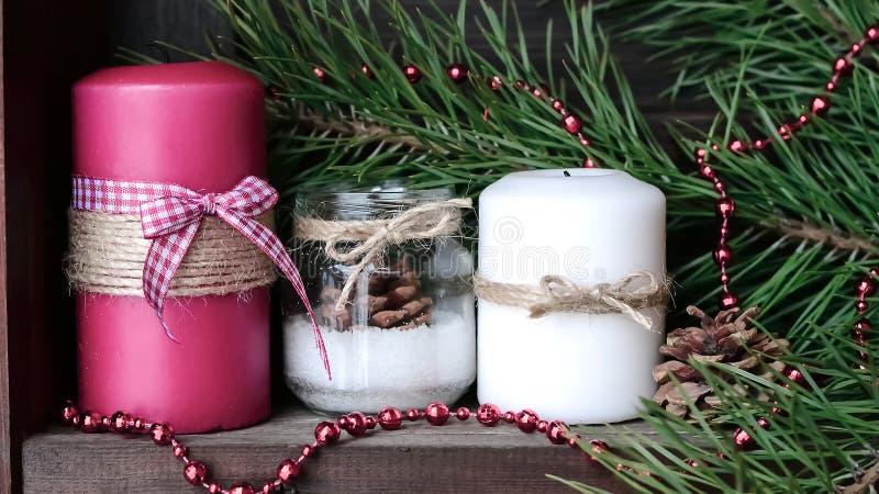 Candela sulla tavola vicino all'albero di Natale Regalo ed agrifoglio fotografia stock