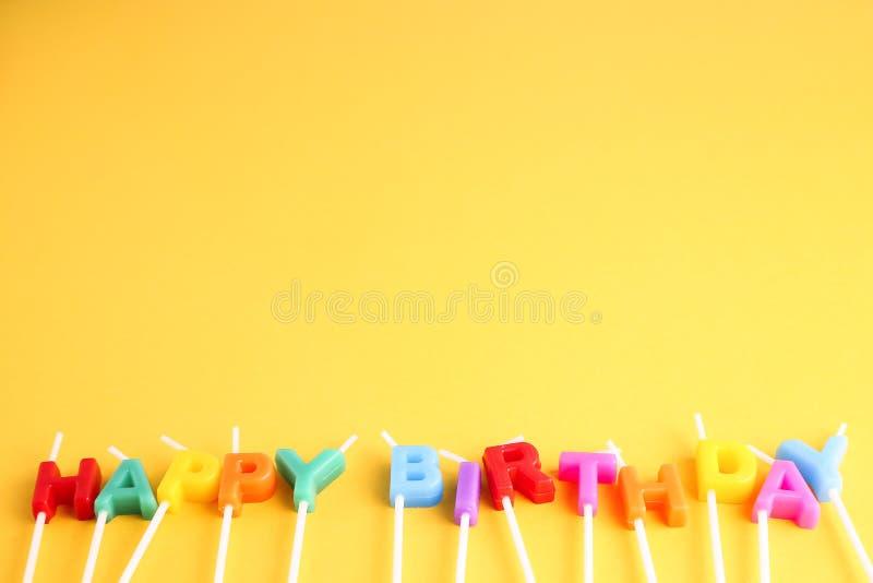 Candela variopinta di compleanno su fondo giallo immagini stock