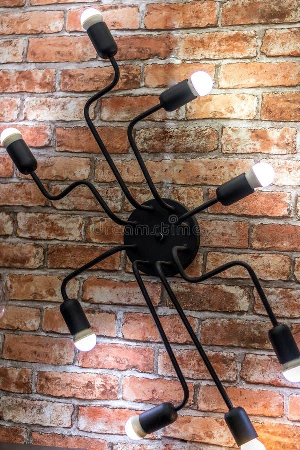 Candelabro da parede sob a forma de uma aranha em uma parede de tijolo Estilo do s?t?o fotografia de stock