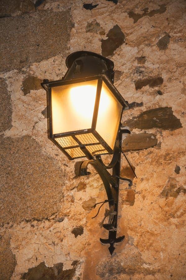 Candelabro de parede do metal do estilo antigo colado à parede de pedra e à luz suave no crepúsculo em Caceres foto de stock