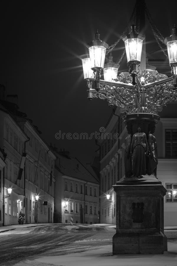 Candelabro storico ed ornamentale del gas in via nevosa di Praga immagine stock