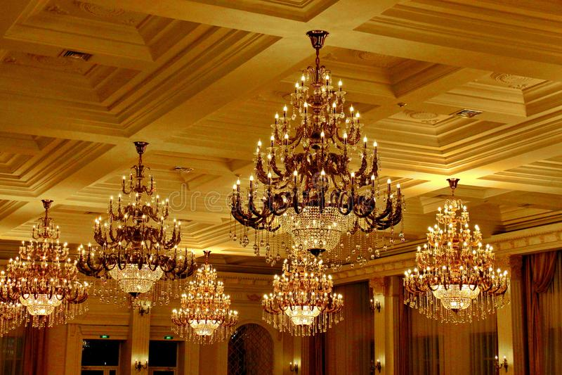 Candelabros de cristal do grande vintage dourado no teto no salão rico foto de stock royalty free