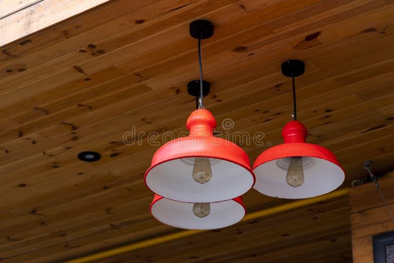 Candelabros vermelhos modernos feitos do metal no teto fotos de stock
