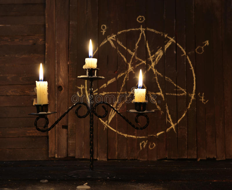 Candelabrum against pentagram background. Candelabrum with burning candles against wooden background with pentagram. Black magic ritual or scary halloween rite stock image