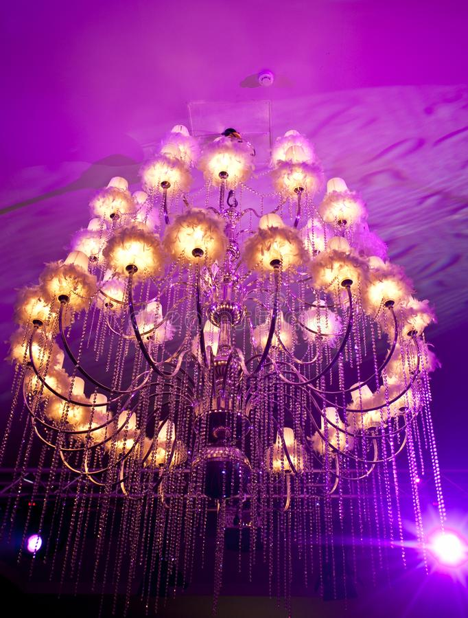 Large candelabrum in a wedding hall. A candelabrum on a purple roof royalty free stock photography