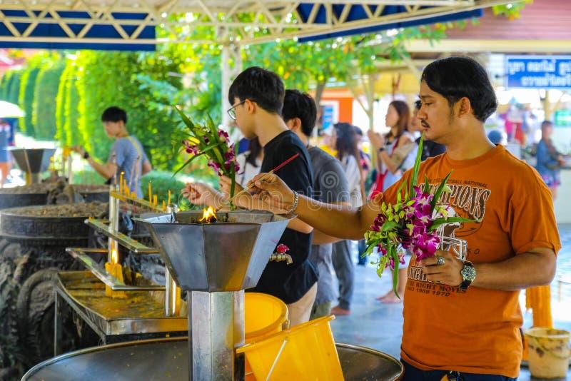 Candele asiatiche degli uomini e delle donne, bastoni di incenso, fiori per adorare il Buddha immagine stock
