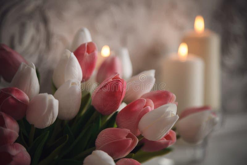 Candele brucianti con i tulipani rosa e bianchi su fondo grigio immagine stock libera da diritti