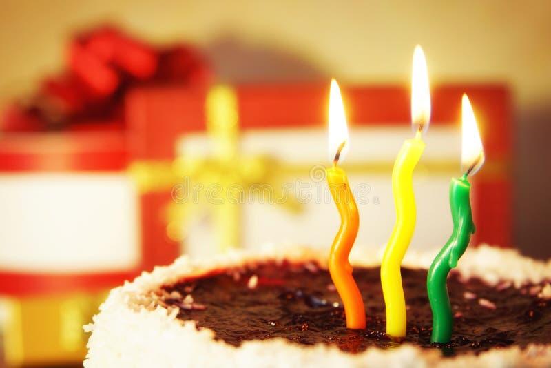 Candele brucianti e torta di compleanno con i regali fotografie stock libere da diritti