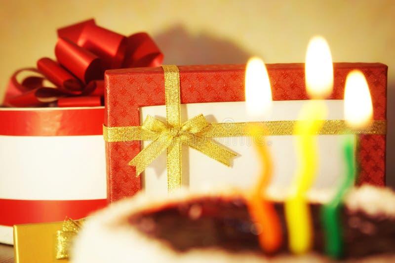 Candele brucianti e torta di compleanno con i regali su fondo fotografia stock