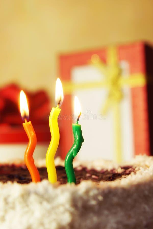 Candele brucianti multicolori e torta di compleanno con i regali fotografie stock libere da diritti