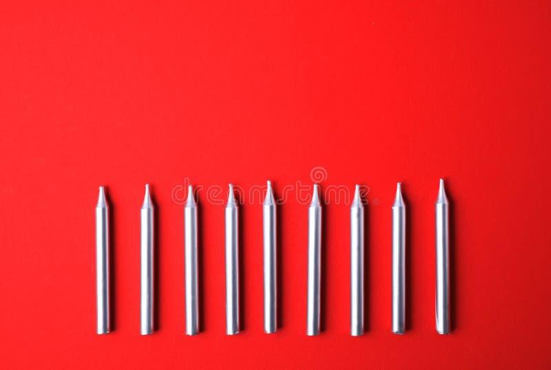 Candele d'argento di compleanno su fondo rosso, spazio per testo fotografia stock