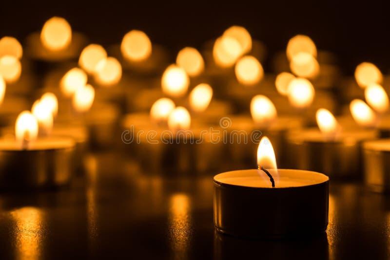 Candele di Natale che bruciano alla notte L'estratto esamina in controluce la priorità bassa Luce dorata della fiamma di candela fotografia stock libera da diritti