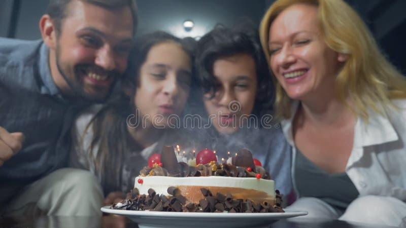 Candele di salto sorridenti felici del ragazzo sulla sua torta di compleanno bambini circondati dalla loro famiglia Torta di comp immagini stock libere da diritti