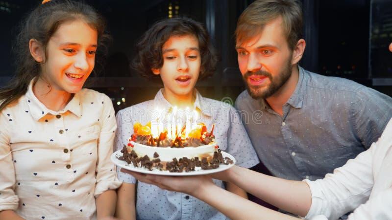 Candele di salto sorridenti felici del ragazzo sulla sua torta di compleanno bambini circondati dalla loro famiglia Torta di comp fotografia stock libera da diritti