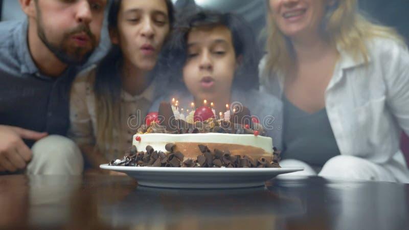 Candele di salto sorridenti felici del ragazzo sulla sua torta di compleanno bambini circondati dalla loro famiglia Torta di comp fotografia stock