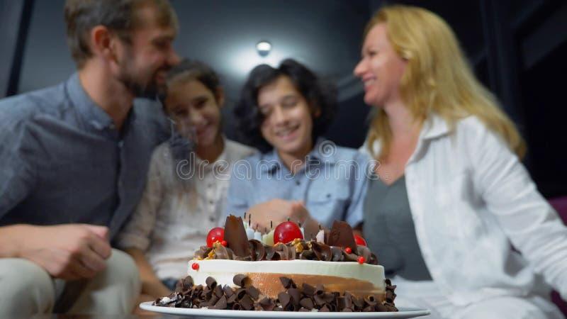 Candele di salto sorridenti felici del ragazzo sulla sua torta di compleanno bambini circondati dalla loro famiglia Torta di comp immagine stock